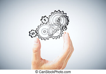 Man's hand holding a the gears