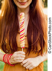 Beautiful young red-haired girl holding a long Lollipop