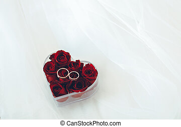 wedding gold rings on red rose petals heart shaped