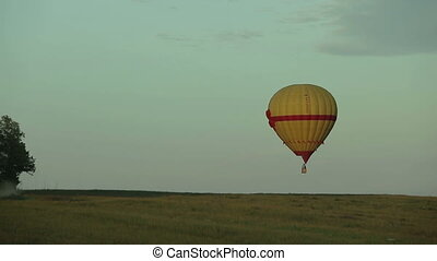 Hot air balloon flying over field in countryside