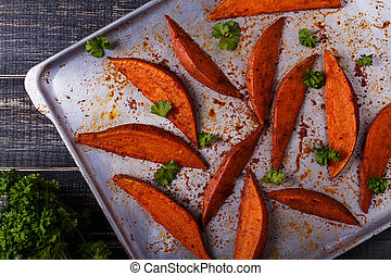 Homemade cooked sweet potatoes with spices and herbs. -...