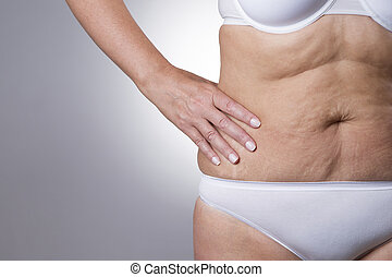 Flabby stomach of an elderly woman close-up on a gray...