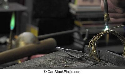 a jeweler creates a bracelet - shaping work and assembly of...