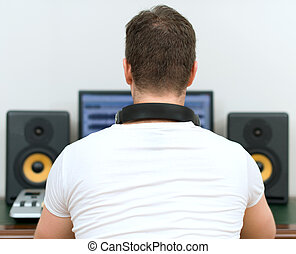 Male sound producer in recording studio. Back view. Space...