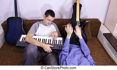 Creative happy couple playing guitar and keyboards