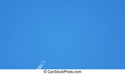 Airplane flying high - Contrails in the blue sky Boeing 777...