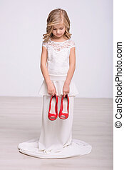 Cheerful little girl holding red shoes - My size. Pleasant...
