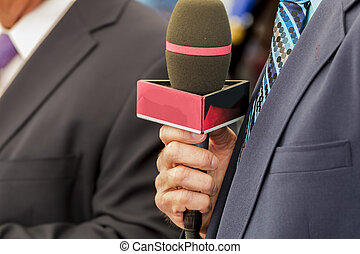 Television Commentator - Television announcer holding a...