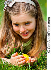 Child with bow on head find easter egg outdoor - Happy...