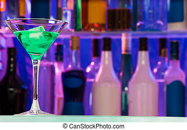 Cocktail glass with green alcohol drink in bar