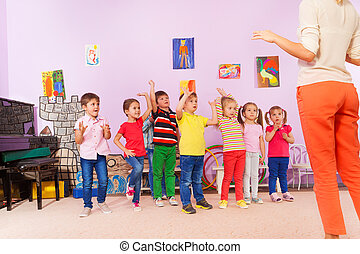 Group of kids repeating exercise after teacher