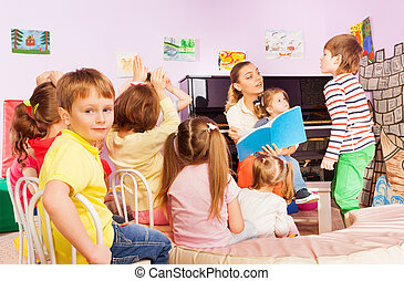 Kids listen to teacher reading book in class - Large group...