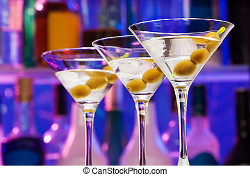 Several cocktail glasses with olives in the bar