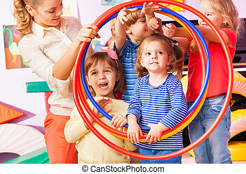 Kids boys and girls look though hoop - Teacher and group of...