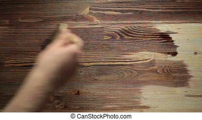 Paint brush painting wooden table with wood stain - Paint...