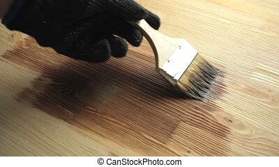 Man painting wooden floor mordant brushing handmade