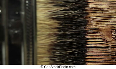 Paint brush painting wooden table with wood stain - Close up...