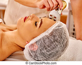 Young woman receiving electric facial massage - Close up of...