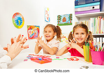 Two girls doing finger exercises as her teacher - Two...