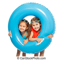 Caucasian girls looking out big blue rubber ring