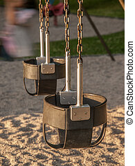 Empty Bucket Swings - Two empty bucket seat swings in a...