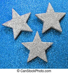 three large silver stars on bright blue glittery background...