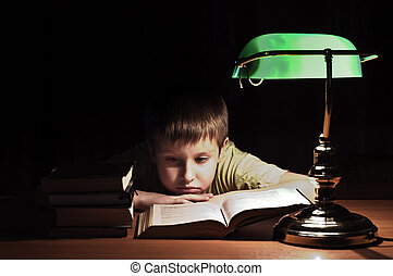 Library boy reads book - boy reads book in dark room under...