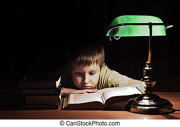 Library boy reads book - boy reads book in dark room under...