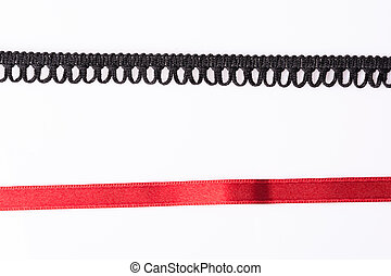 Lace trim ribbon over white. Black and red
