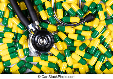 Medication capsules and stethoscope in fill frame format -...