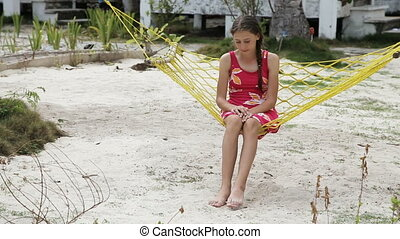 Young girl swinging in a hammock - young girl sitting and...