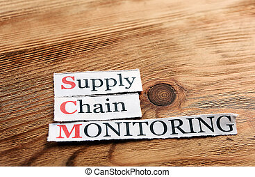 SCM Supply Chain Monitoring acronym on paper on wooden...