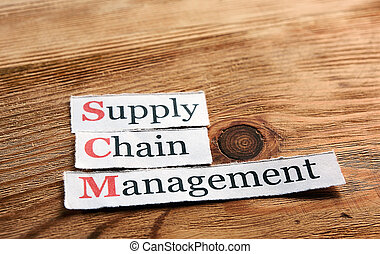 SCM Supply Chain Management acronym on paper on wooden...