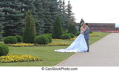 Wedding shot of bride and groom in park summer