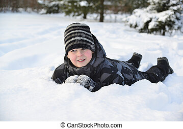 Teen boy lies on   snow in the winter forest