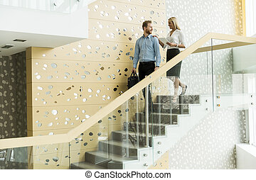 Young couple in the office - Young couple on stairs in the...