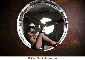 Beautiful young sexy woman in a white helmet posing with...
