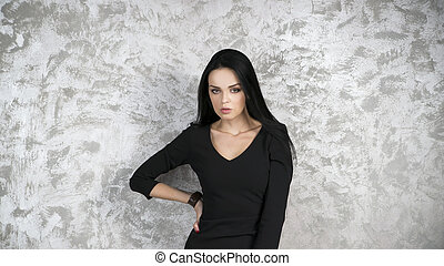 Portrait of a beautiful young woman in a black dress on abstract gray background