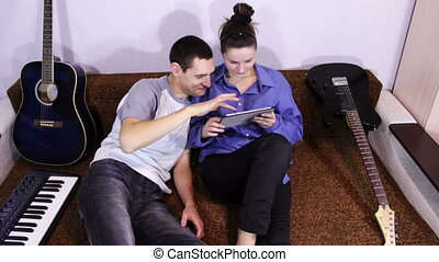 Happy Young Couple using Tablet PC on the couch - Young...