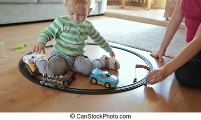 Little boy with mother playing with toy train, HD
