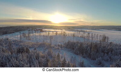 Flying above forest and farm in winter at sunset - Camera...