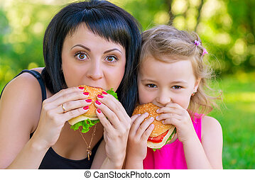portrait of mother with her daughter in the park with burgers