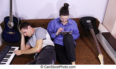 Happy Young Couple using Tablet PC and play piano - Young...