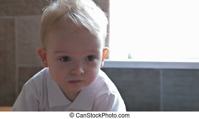 Little beautiful blond boy eating sweeets at the kitchen, HD