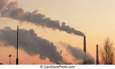 Smoke from factory chimneys over grey sky and clouds