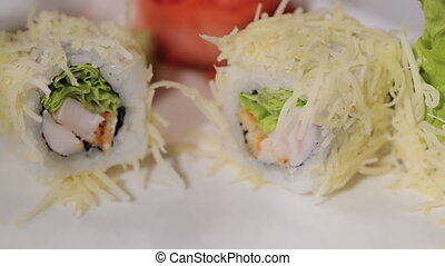 Unfolding sushi rolls on a plate. cheese, shrimp and rice,...