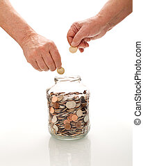 Senior hands collecting coins in a glass jar - saving for...