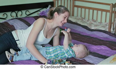Mother and son having tickle fight in bed.