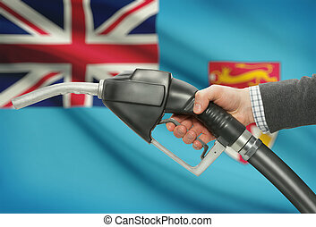 Fuel pump nozzle in hand with national flag on background -...