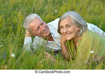 mature couple lying on grass - Loving mature couple lying on...